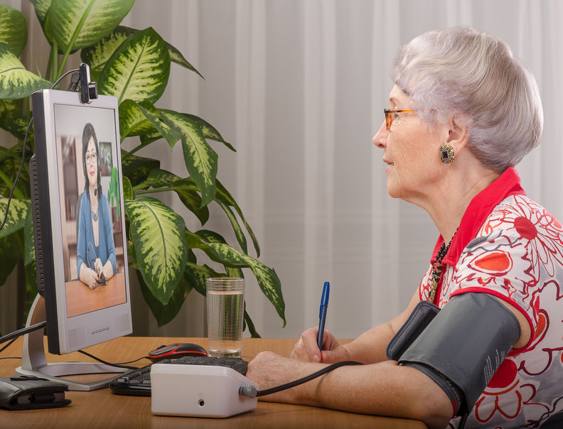 Woman measuring blood pressure during a virtual doctor appointment