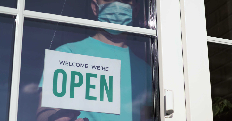 Doctor with mask on flipping an 'open' sign