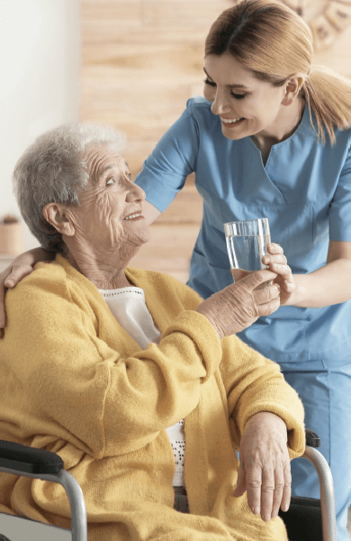 Nurse handing glass of water to woman in wheelchair
