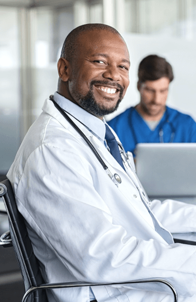 Male doctor sitting in a chair smiling